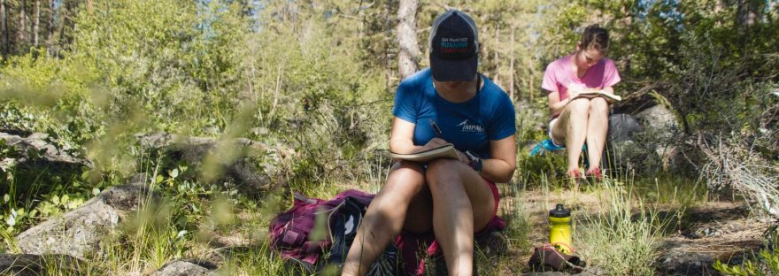 Erin Bank dressed in running clothes, wearing a hat, sitting on a rock in the woods, writing in a journal on her lap