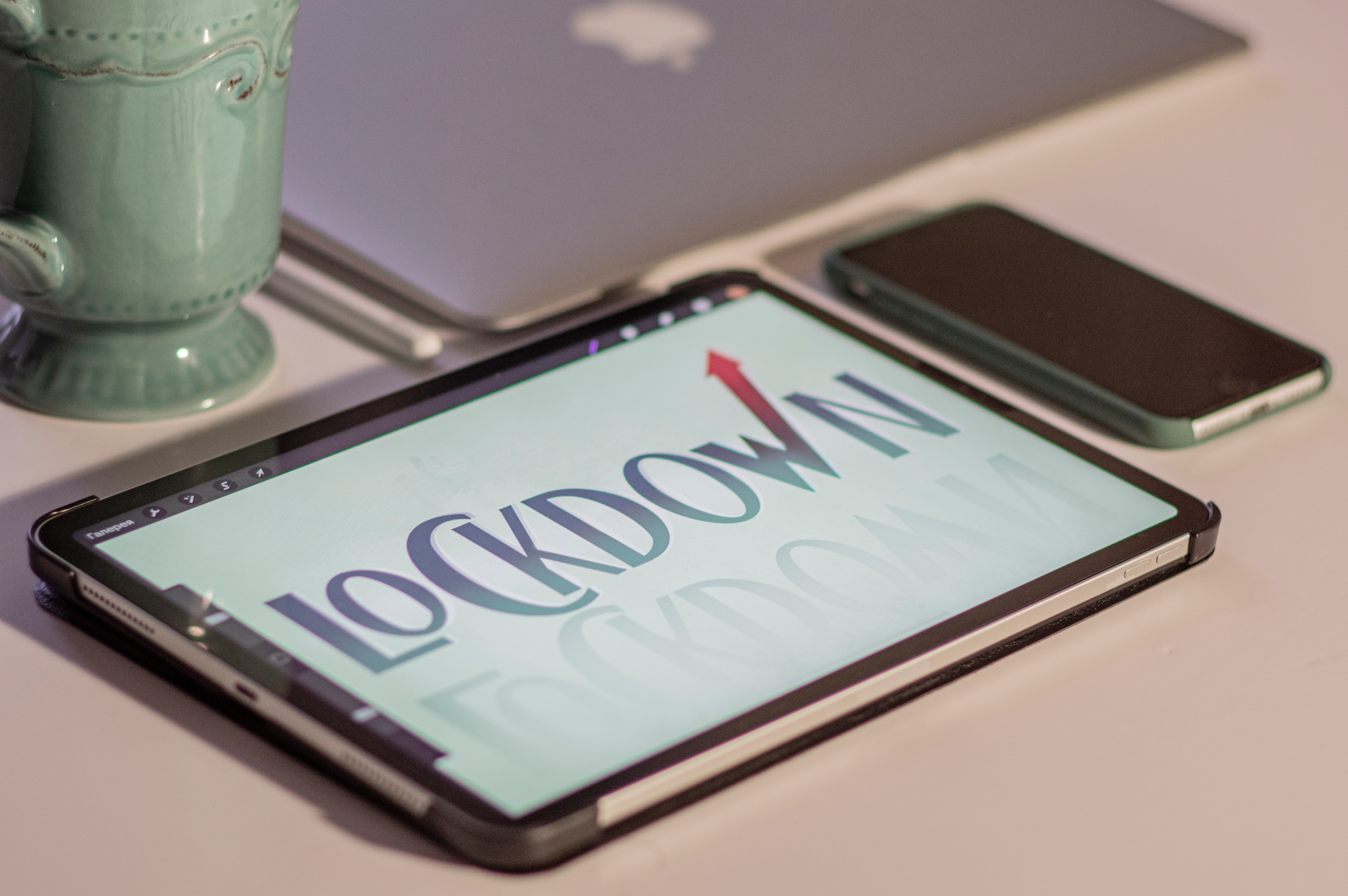 """Image of a tablet screen with """"Lockdown"""" displayed, on a table next to a phone and mug."""