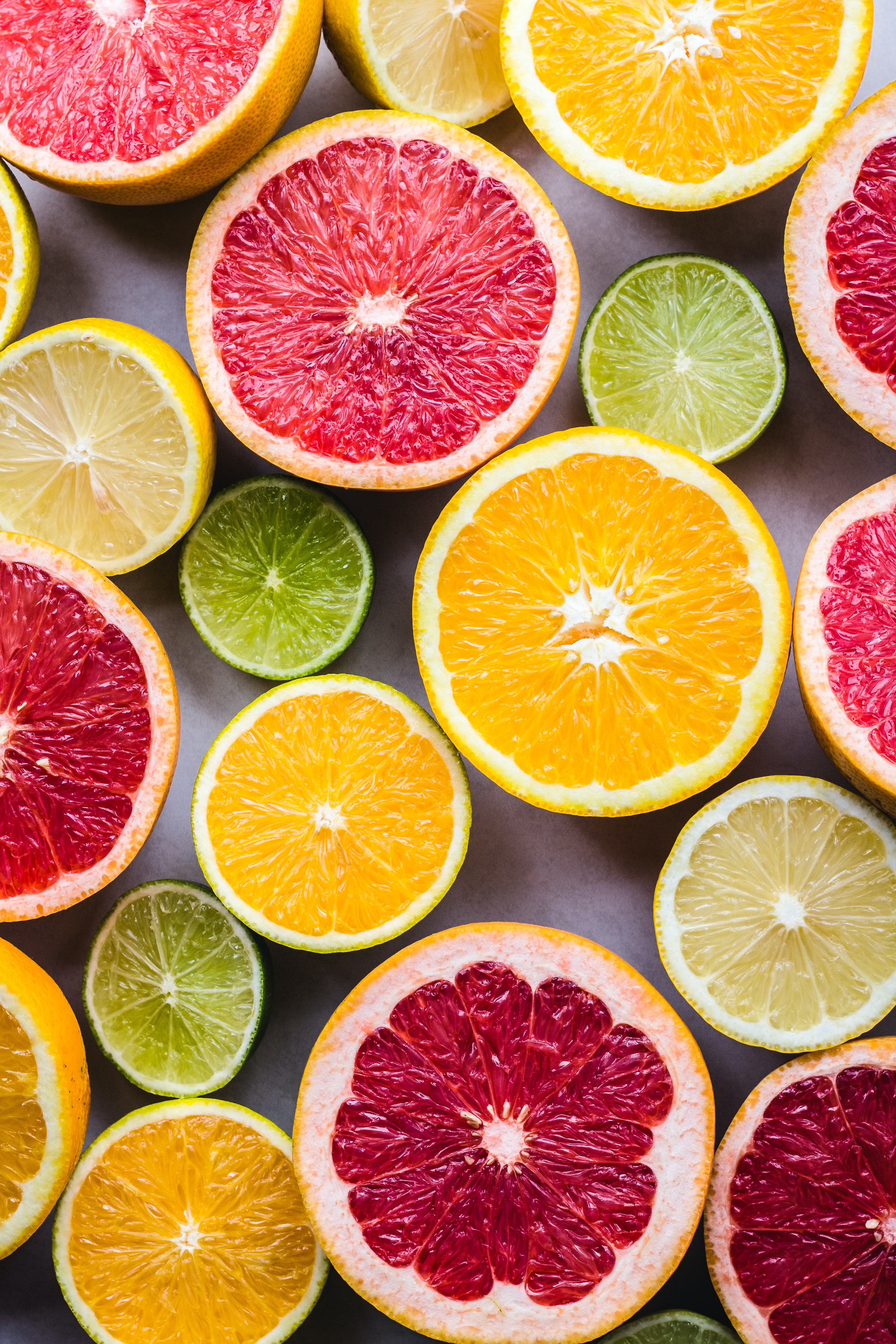 photo of various citrus fruit cut in half with insides facing up